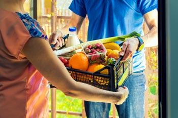 Mann übergibt Obst-und Gemüsekiste an der Haustür