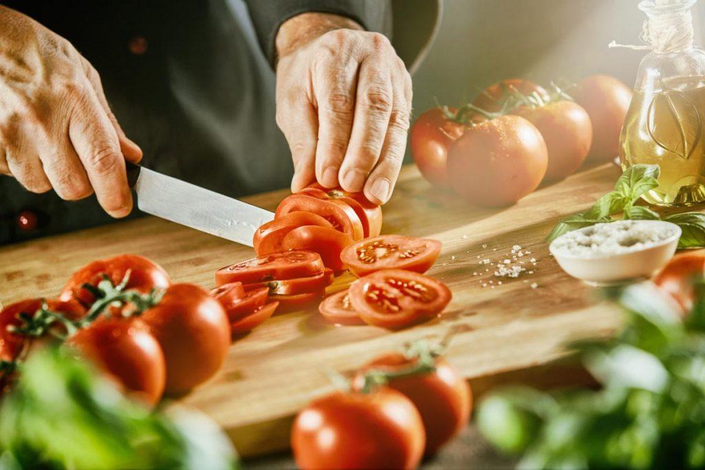Koch schneidet Tomaten