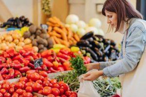 Frau kauft im Gemüseladen ein